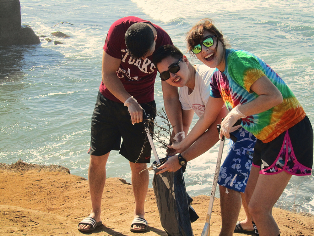 people posing for camera picture of them and trash picker upper items beach cleanup san diego coastkeeper sunset cliffs